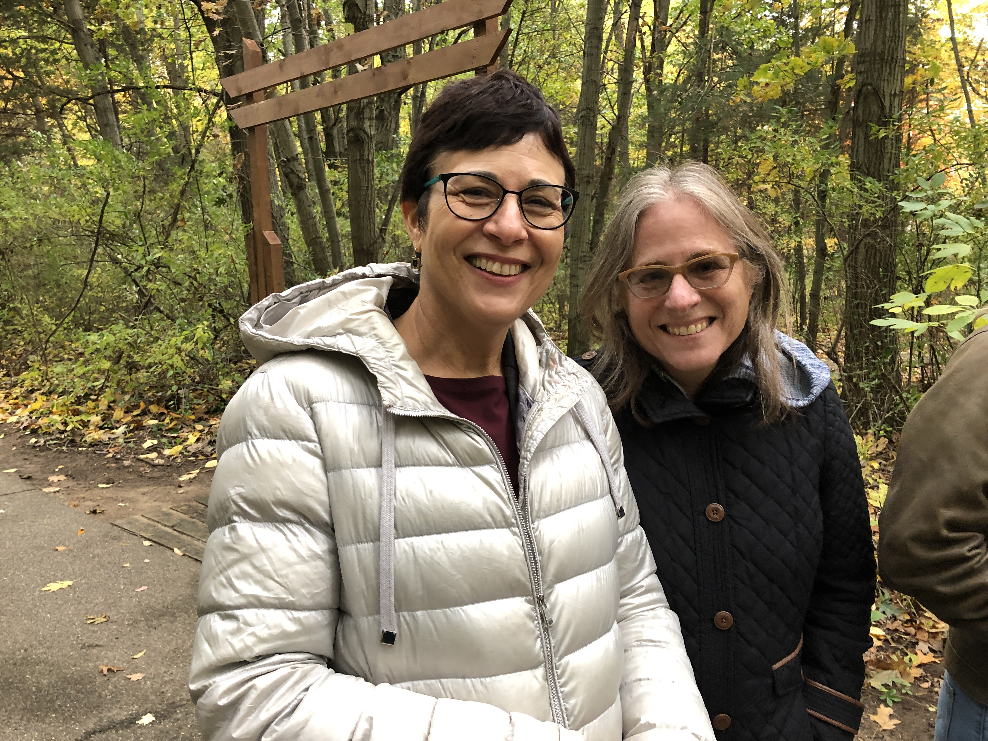 Team members Tali and Renee stand together on a wooded trail during our 2019 planning retreat