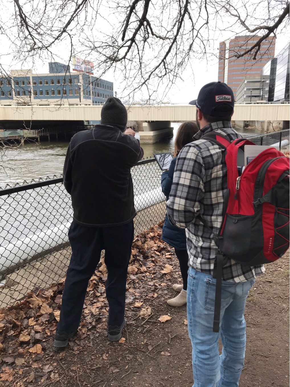 Three teachers stand next to the Grand River in winter, with city buildings in the background.